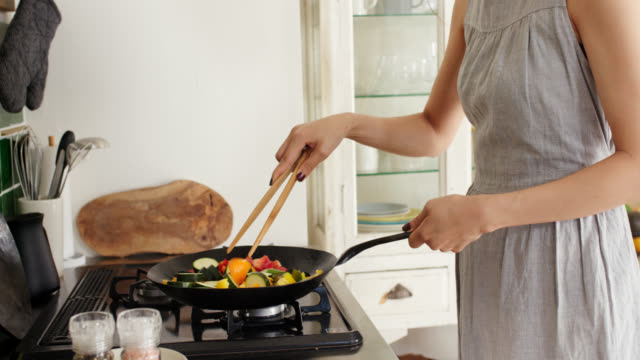 close-up of a young woman cooking stir fry in wok - healthy eating stock videos & royalty-free footage