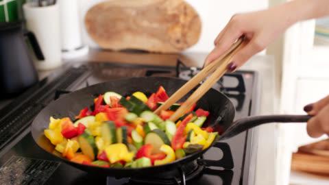 vídeos de stock, filmes e b-roll de close-up de uma mulher nova que cozinha vegetais em um wok - cozinha doméstica