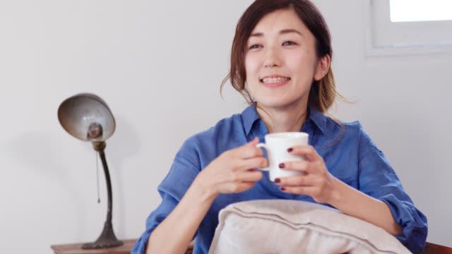 ソファーでコーヒーを飲んでいて、フレームの外で誰かに話しかけている若い女性のクローズアップ - くつろぐ点の映像素材/bロール
