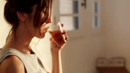 Close-up of a young woman drinking tea at home