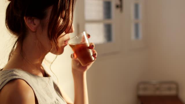 自宅でお茶を飲む若い女性のクローズアップ - カップ点の映像素材/bロール