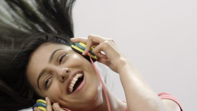 Close-up of a young woman listening to music with headphone