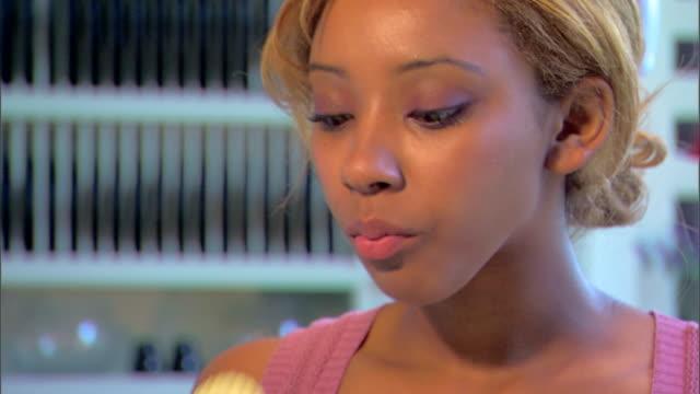 vídeos de stock, filmes e b-roll de close-up of a young woman standing in her kitchen eating potato chips. - snack salgado