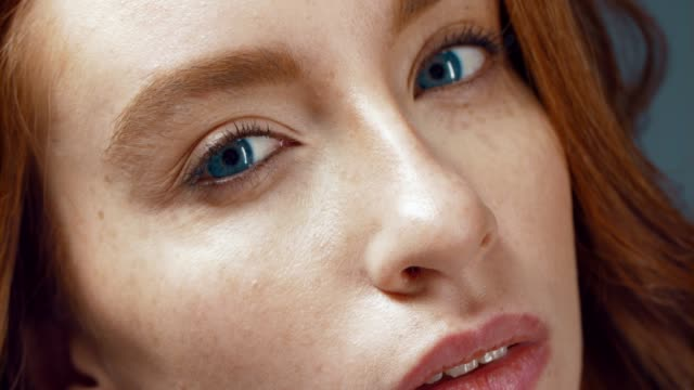 stockvideo's en b-roll-footage met een close-up van de ogen van een jonge vrouw, ze staart in de camera, dan is haar ogen helderder als ze glimlacht - roodhoofd