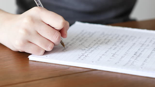 close-up of a young woman's hands writing on a pad of paper - adult stock videos & royalty-free footage