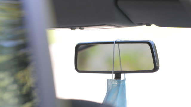 close-up of adult man hanging protective face mask on rear view mirror in car - rear view mirror stock videos & royalty-free footage