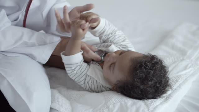 聴診器、スローモーションでアフリカの赤ちゃんの検診のクローズアップ - 小児科医点の映像素材/bロール