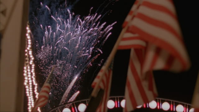 Close-up of American flags on a column and lights and fireworks in the background.