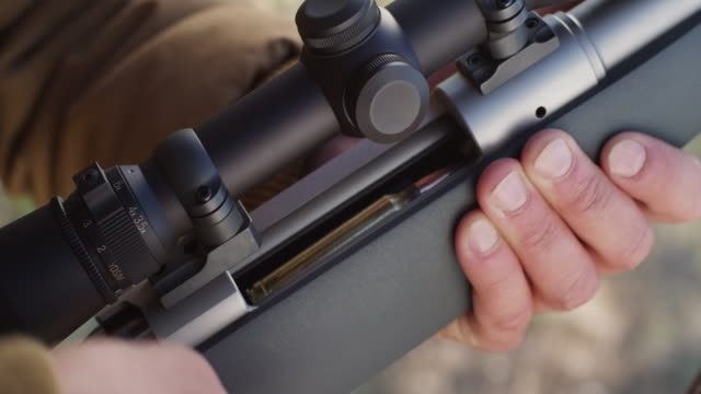 closeup of ammunition cartridges as they are inserted in the clip of a rifle. - munition stock-videos und b-roll-filmmaterial