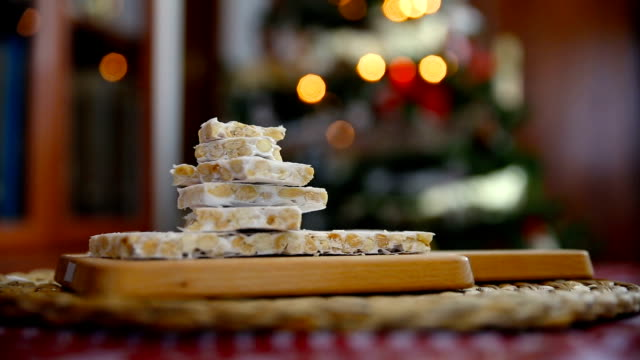 Close-up of an almond nougat next to the Christmas tree in a home room
