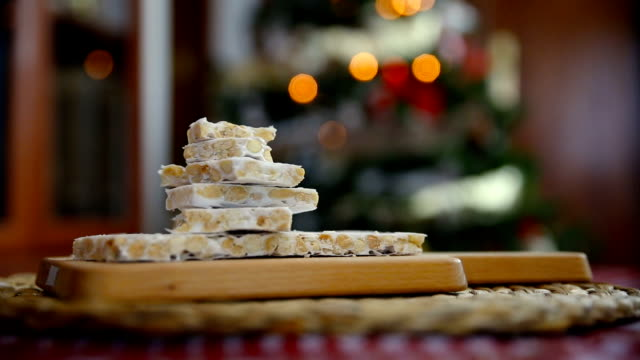 close-up of an almond nougat on a dining table and the lights of the Christmas tree behind