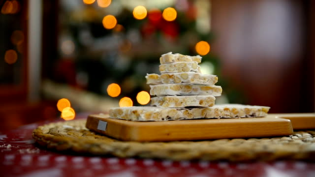 close-up of an almond nougat on a dining table with the lights of the Christmas tree behind
