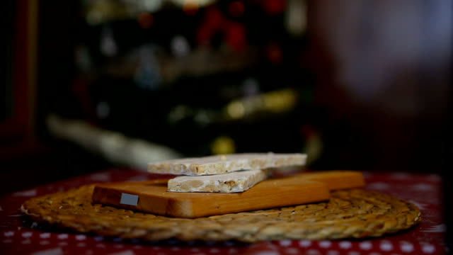 close-up of an almond nougat on a table with the lights of the Christmas tree behind