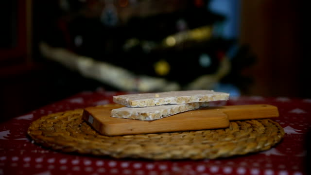 Close-up of an almond nougat with the lights of the Christmas tree behind