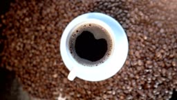 A close-up of an americano coffee in a white cup amongst brown coffee beans