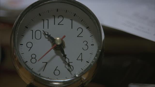Close-up of an analog alarm clock reading 10:25.