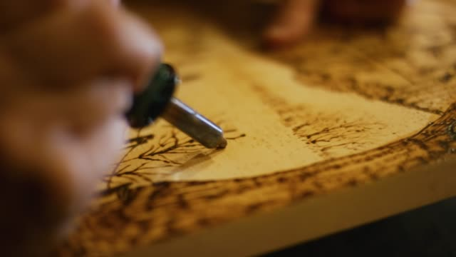 close-up of an artist using a wood burning pen to burn a design into a cross section of wood - art and craft stock videos & royalty-free footage