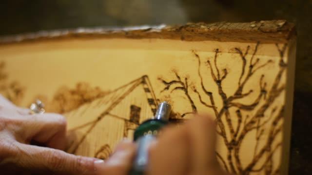 vídeos y material grabado en eventos de stock de primer plano de un artista que utilizando una pluma de leña para quemar un diseño en una sección transversal de la madera - work tool