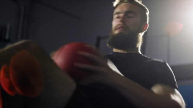 close-up of an attractive caucasian man in his twenties with a beard performs twisting ab/abdominal exercises with a medicine ball in a dramatically lit gym (medium tight shot) - twisted stock videos & royalty-free footage