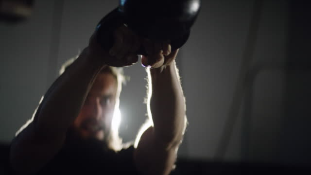 close-up of an attractive caucasian man in his twenties with a beard performing kettlebell swings in a dramatically lit gym (medium shot) - kettlebell stock videos & royalty-free footage