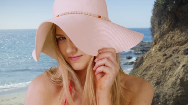 vídeos de stock, filmes e b-roll de closeup of an attractive woman smiling on a sunny beach - hat