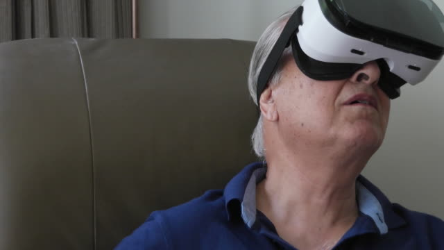 Close-up of an elder gentleman wearing virtual reality heat-set and looking around and speaking