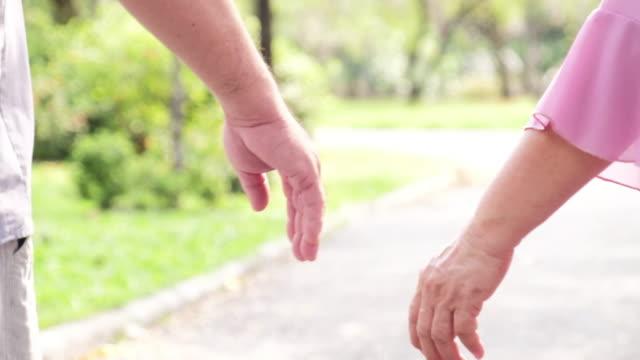 vídeos de stock e filmes b-roll de close-up of an elderly couple holding hands and walking together - seguro médico