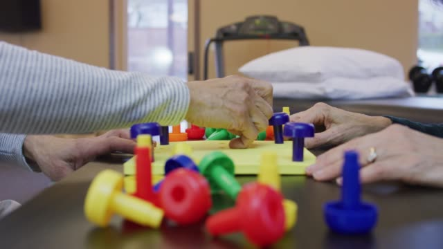 closeup of an older ethnic woman at a session with acaucasian occupational therapist - rehabilitation center stock videos & royalty-free footage