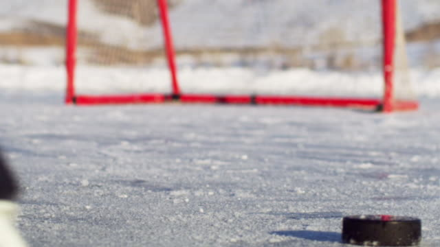 Close-up of an outdoor ice-rink and hockey net.  A slow-motion shot is taken as the skater skates forward the back of the skates are visible.