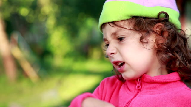 Close-up of an unhappy child frowns from bad smell