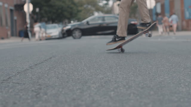 A closeup of an unrecognizable man skateboarding through the streets of Brooklyn in slow motion.