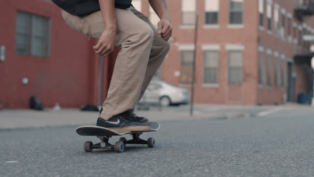 Closeup of an unrecognizable man's feet as he skateboards through Brooklyn city streets - slow motion
