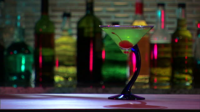 Close-up of as hand takes martini off bar.