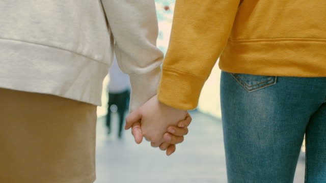 close-up of asia lesbian lgbt couple hand-holding and walking with shopping bags,slow motion - holding hands stock videos & royalty-free footage