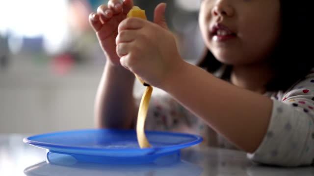 のクローズアップアジアの中国の幼児ピーリング、バナナ肌を最後に食べて - バナナ点の映像素材/bロール