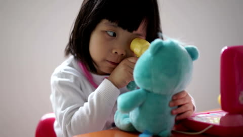 closeup of asian chinese toddler playing pretend doctor with her teddy bear - fantasy stock videos & royalty-free footage