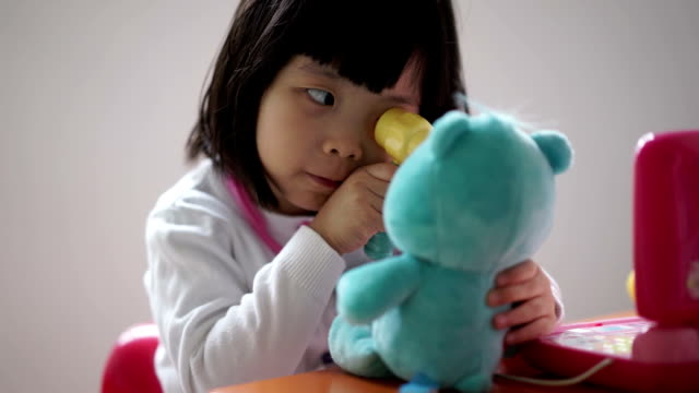 closeup of asian chinese toddler playing pretend doctor with her teddy bear - teddy bear stock videos and b-roll footage
