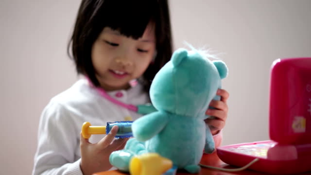 closeup of asian chinese toddler playing pretend doctor with her teddy bear - doll stock videos & royalty-free footage