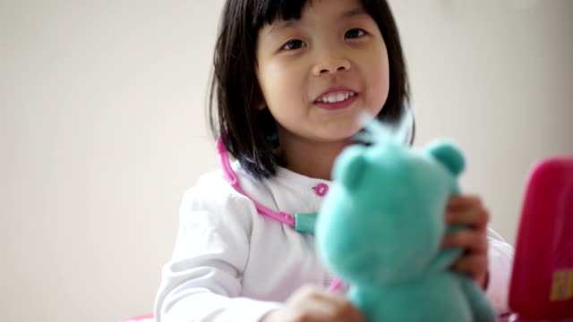Closeup of Asian chinese toddler playing pretend doctor with her teddy bear