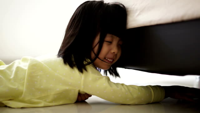 Closeup of Asian chinese toddler trying hard cleaning the floor under the bed