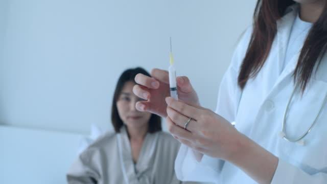 close-up of asian female doctor preparing a syringe,slow motion - ago parte della pianta video stock e b–roll