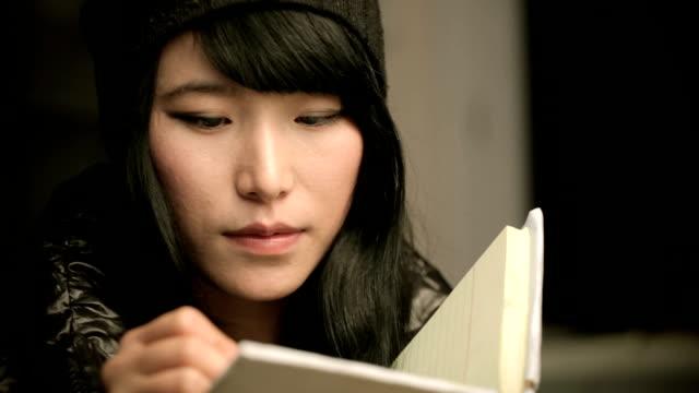 vídeos y material grabado en eventos de stock de primer plano de la joven estudiante asiática escrito en un cuaderno. - aferrarse