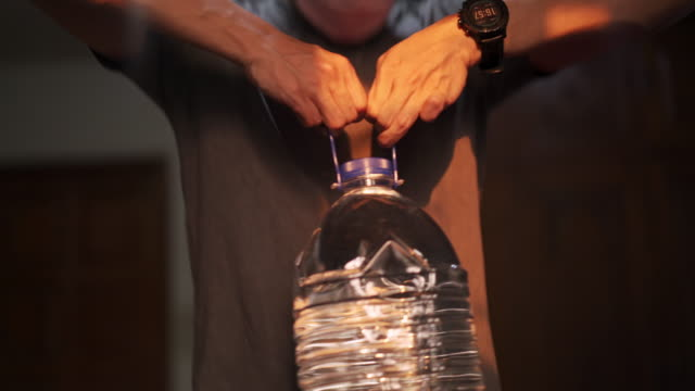 4k close-up of asian man hand working out by using asian man using plastic gallon water bottle instead of gym weights for exercise at home in covid-19 or corona virus situation - sollevare video stock e b–roll