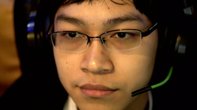 Close-up of Asian Teenager Boy Playing Computer Video Games in His Headset