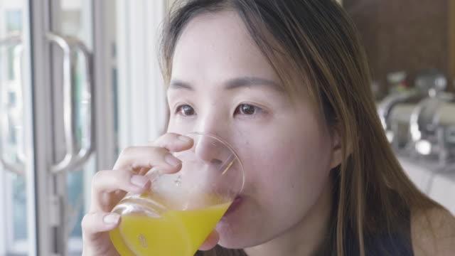 nahaufnahme der asiatischen frau trinkt orangensaft beim frühstück - saft stock-videos und b-roll-filmmaterial