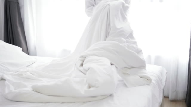closeup of asian woman throwing white blanket on bed - stock video - bedclothes stock videos & royalty-free footage