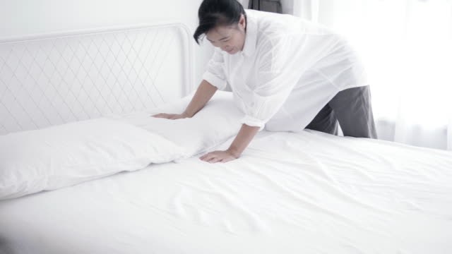 closeup of asian woman throwing white blanket on bed - stock video - blanket texture stock videos and b-roll footage