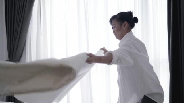 Nahaufnahme der Asiatin werfen weiße Decke auf Bett - Stock video