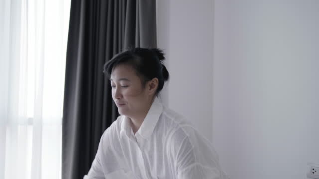 closeup of asian woman throwing white blanket on bed - stock video - soft blanket stock videos and b-roll footage