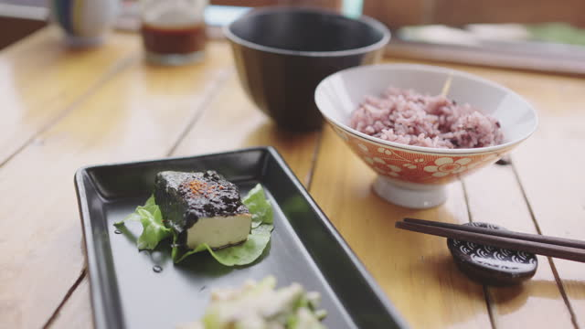 玄米と一緒に豆腐の盛り合わせのクローズアップ。 - 玄米点の映像素材/bロール